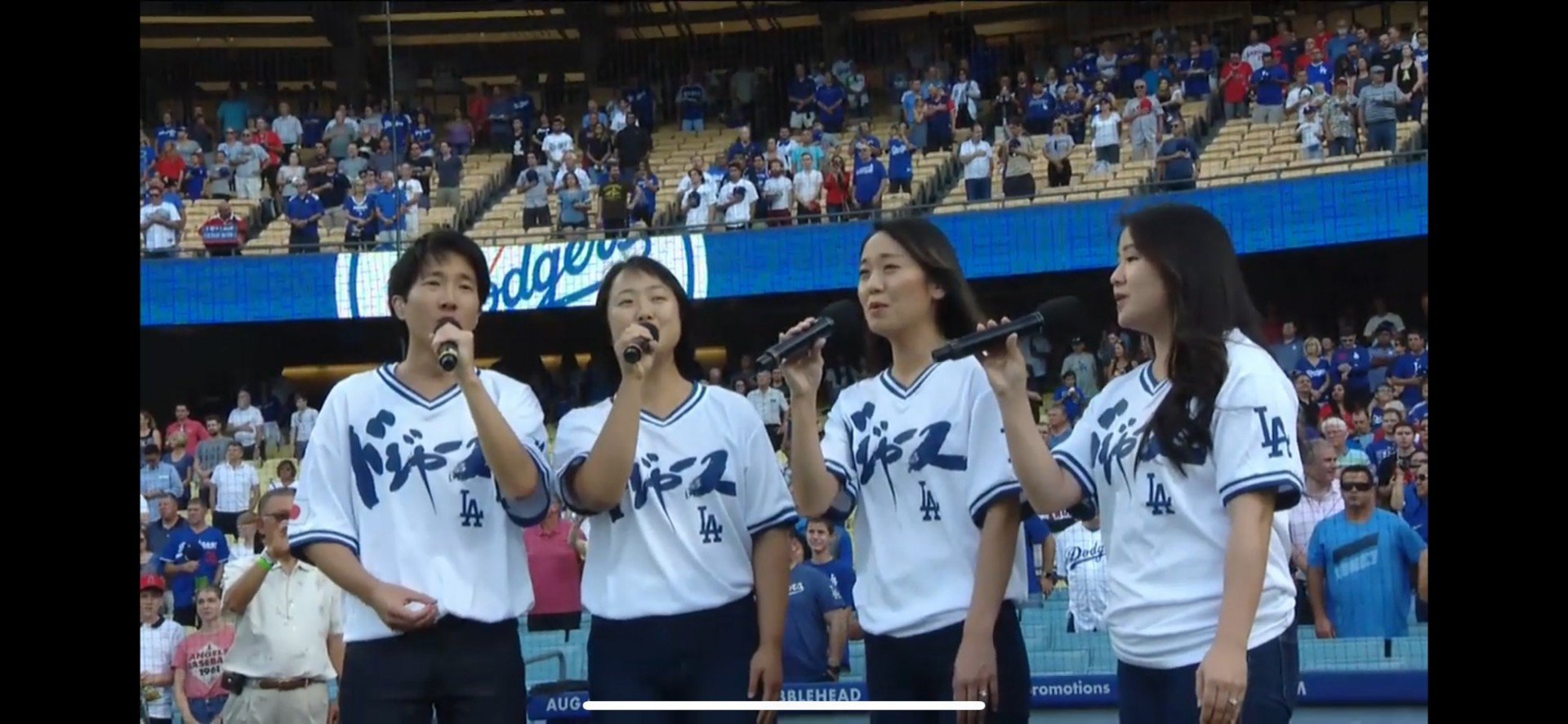 Postdoctoral scientist Michael Murata, PhD, left, sings the Japanese national anthem as part of the a cappella group Grateful Four to open a recent Dodgers game. Photo courtesy of Michael Murata, PhD.