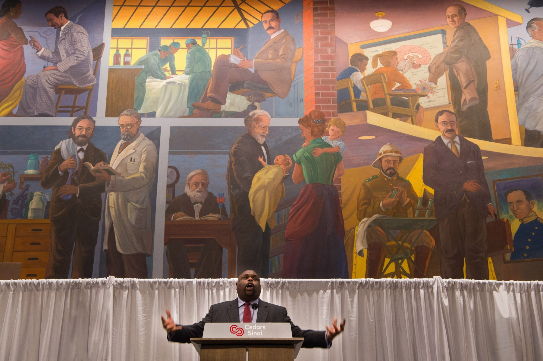 With a mural depicting the history of Jewish medicine in the background, motivational speaker Rick Rigsby, PhD, gave an inspiring keynote address at Cedars-Sinai's 18th Annual Dr. Martin Luther King Jr. Day Celebration. Photo by Cedars-Sinai.