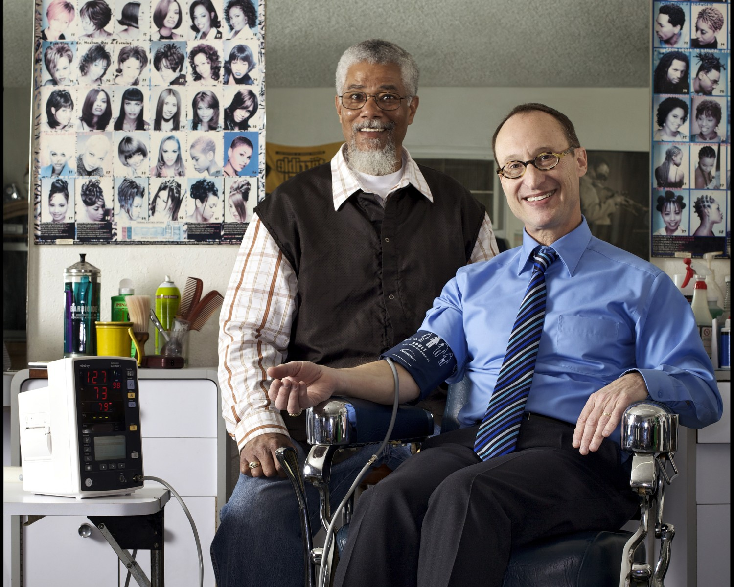 During a barbershop hypertension study, barber Wally Riddle took the blood pressure of Ronald G. Victor, MD.  Photo by Cedars-Sinai.
