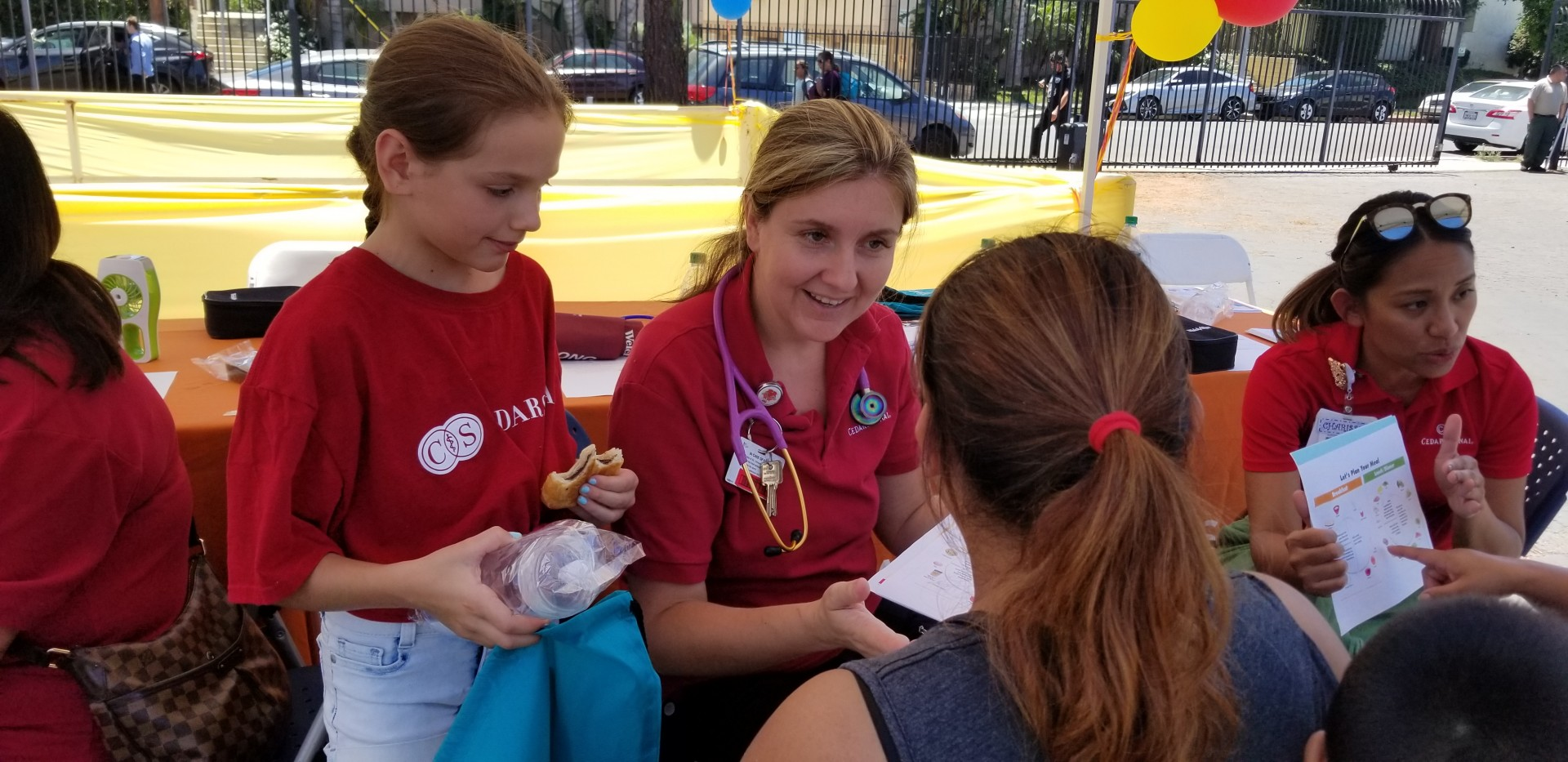 Olena Svetlov, RN, CNS, with stethoscope, and her daughter, Taya, left, help a family get ready for a healthy school year. Photo by Cedars-Sinai.