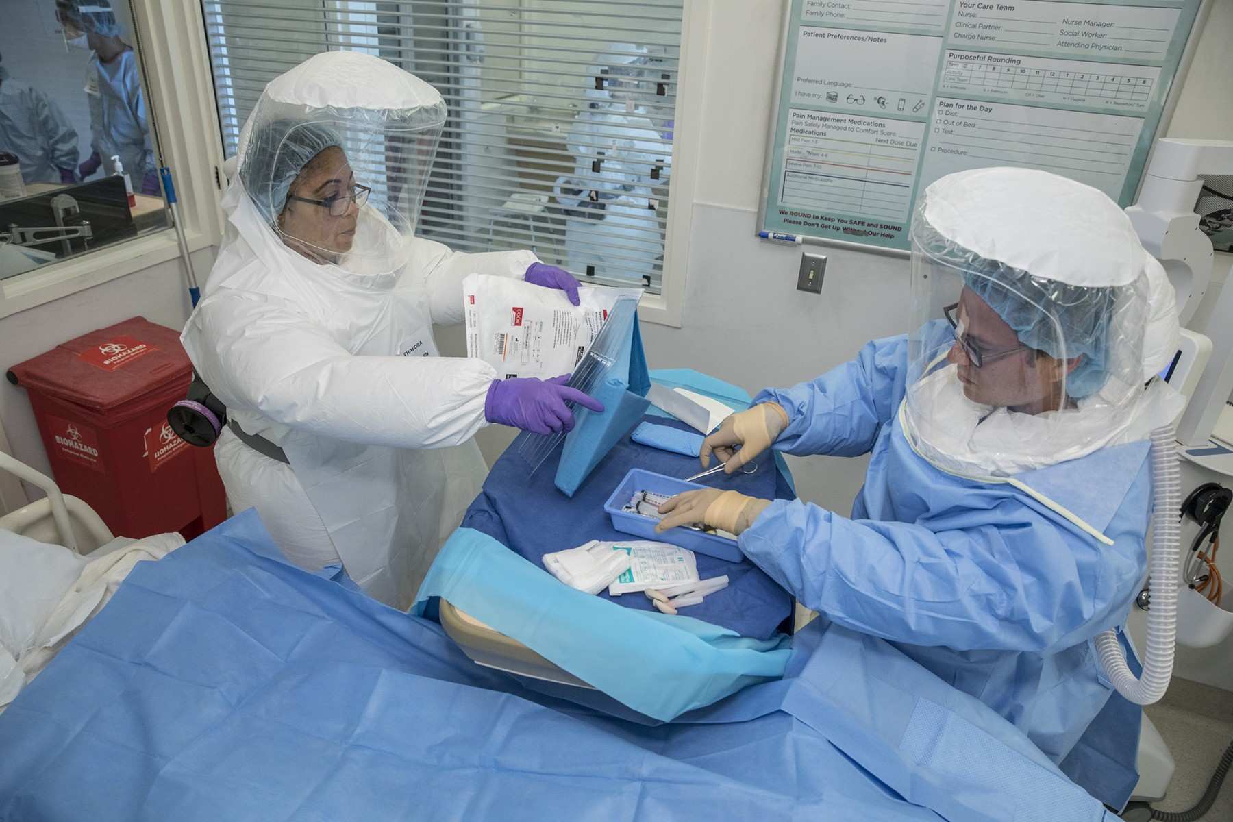 A Phaedra Harris, RN, and Oren Friedman, MD, prepare to do a procedure during a Special Pathogens Response Team  Ebola drill in 2017. Photo by Cedars-Sinai.