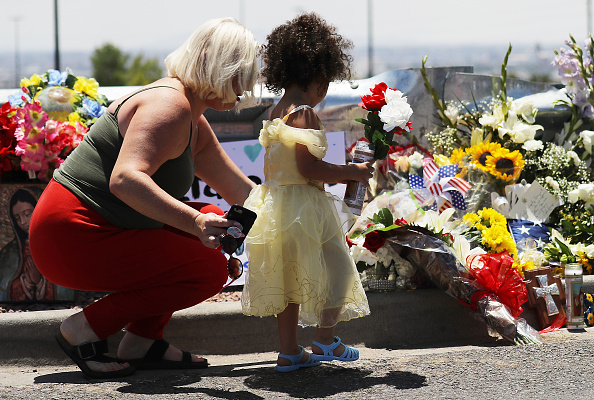 Jessica (L) and Kalani Windham leave flowers and a candle outside Walmart, near the scene of a mass shooting which left at least 20 people dead, on August 4, 2019 in El Paso, Texas.  Photo by Mario Tama/Getty Images.