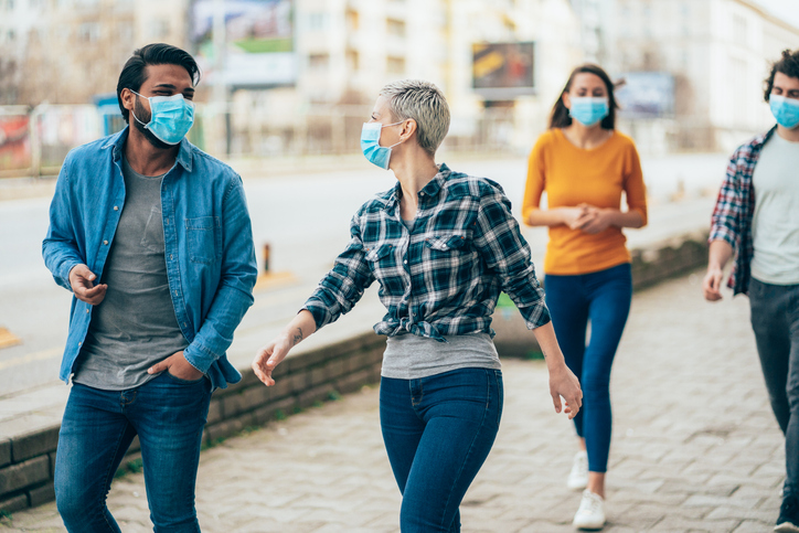 Wearing a mask can contain the respiratory droplets that travel up to 6 feet through the air when we talk, sing, sneeze or cough. Photo by Getty.
