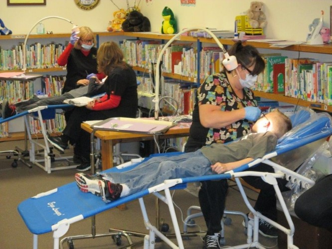 Hygienists and dental assistants treat students in Oregon's public schools as part of a statewide initiative to increase oral health outcomes starting in kindergarten.