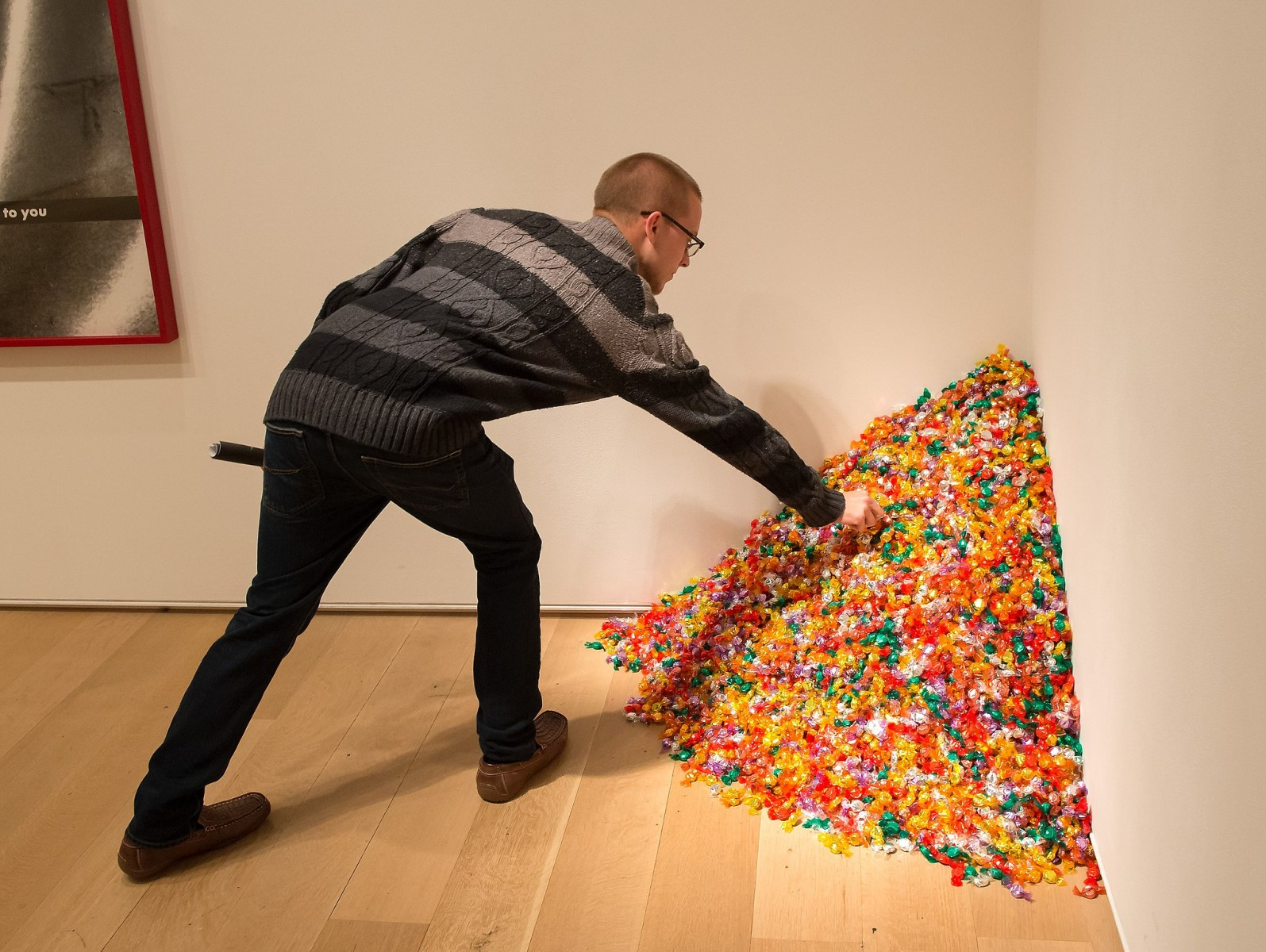 "A man takes a piece of candy from ""Untitled"" (Portrait of Ross in L.A.) by Felix Gonzalez-Torres."