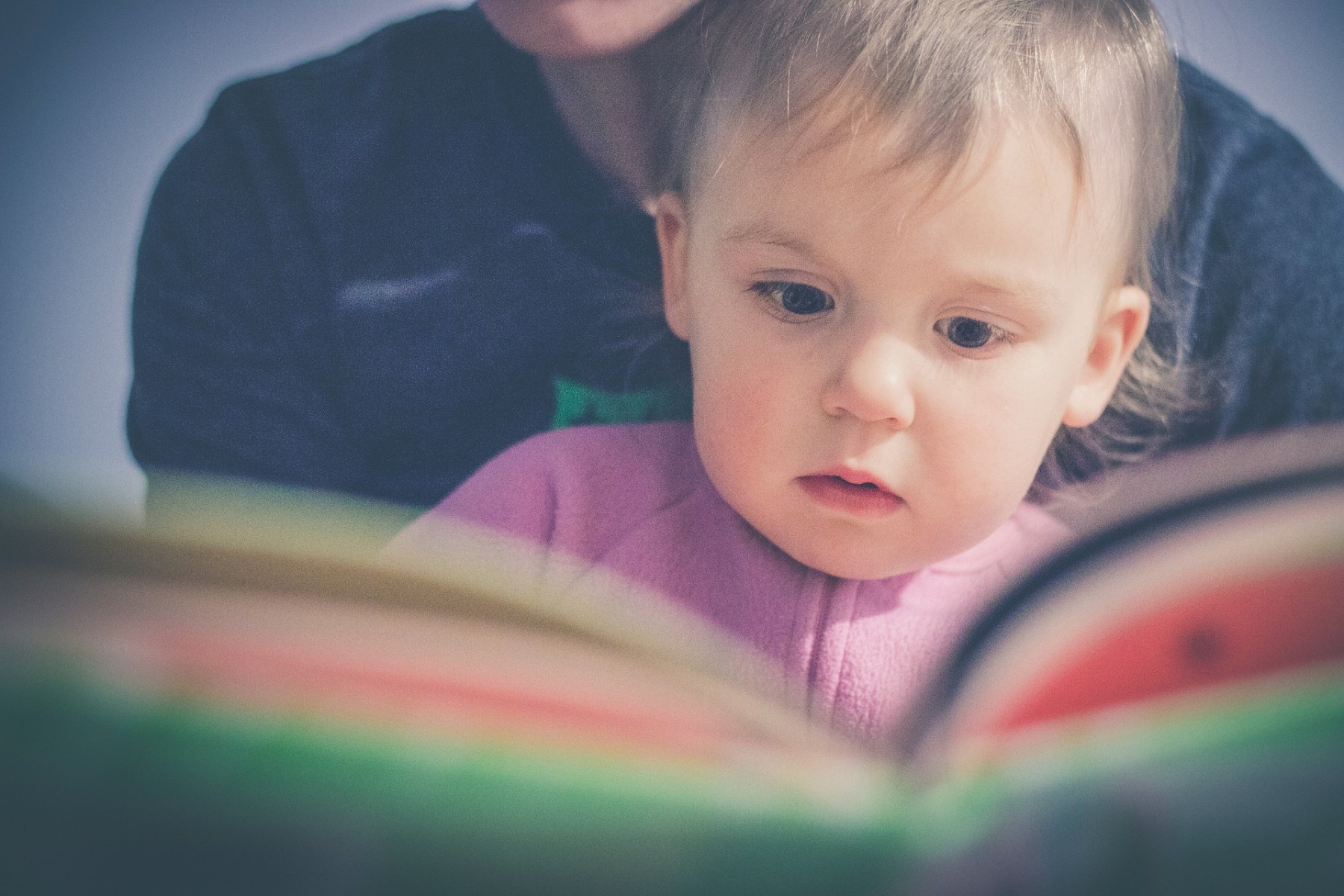 A child watches intently as he is read to