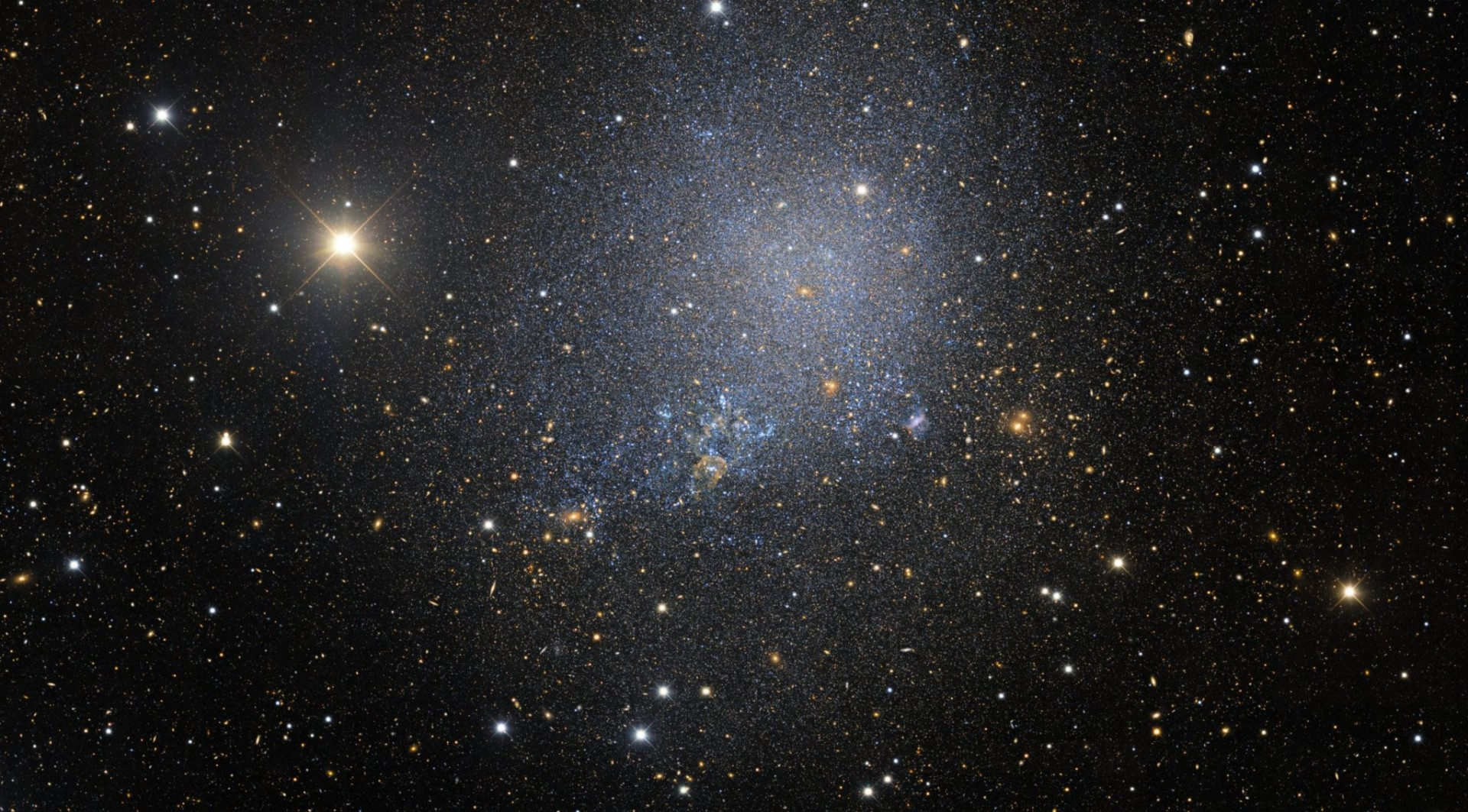 This irregular dwarf galaxy, named IC 1613, and discovered through the  Dark Energy Survey, contains some 100 million stars (bluish in this portrayal). It is a member of our Local Group of galaxy neighbors, a collection which also includes our Milky Way, the Andromeda spiral and the Magellanic clouds.
