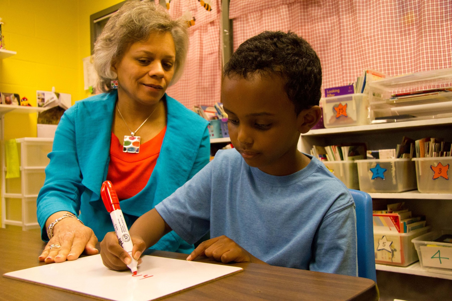 A teacher engages a first-grader in Reading Recovery