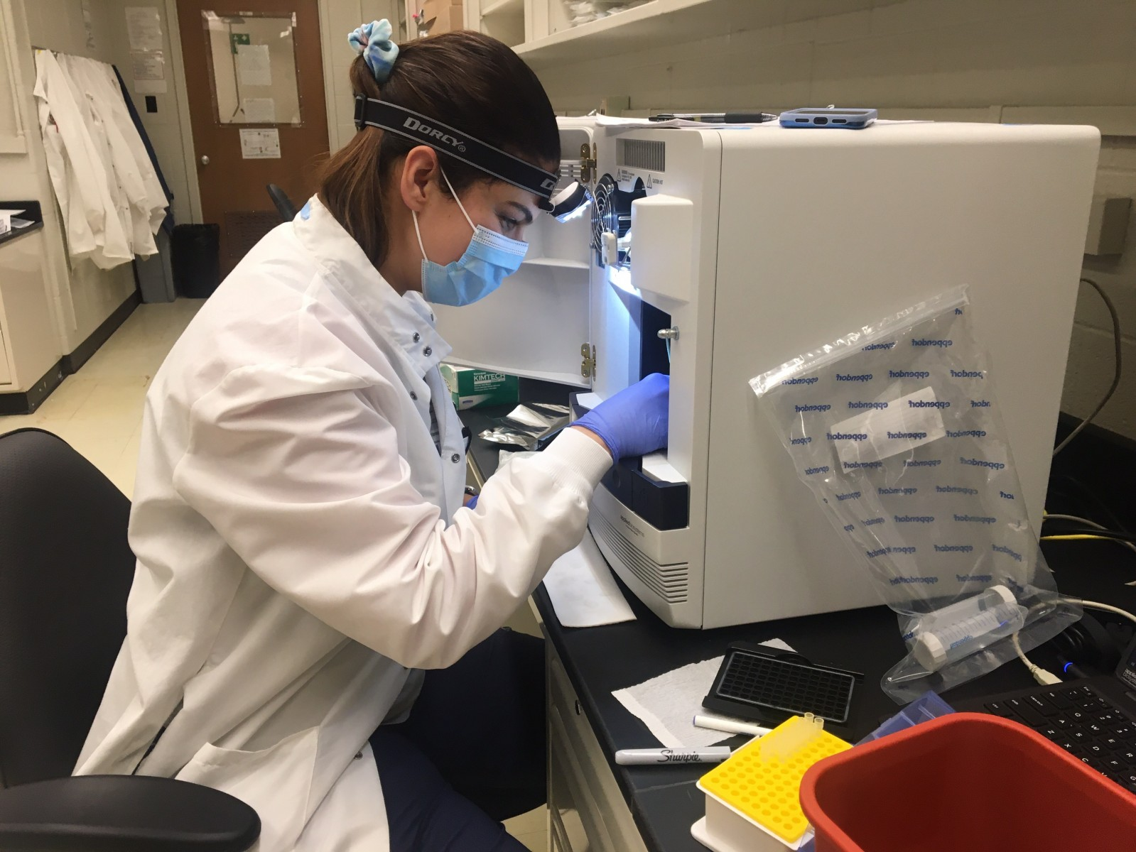 "Marianela ""Mary"" Feliu, M.S. , a medical student at Ohio State, performs background calibration on one of the 20 PCR analyzers at the Applied Microbiology Services Lab. The machines read COVID-19 test results and can analyze 93 samples at a time."