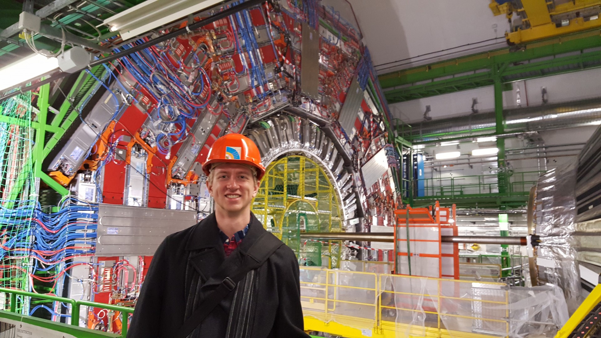 Tony Lefeld, a doctoral student in physics at Ohio State, stands in front of CMS detector at the Large Hadron Collider.