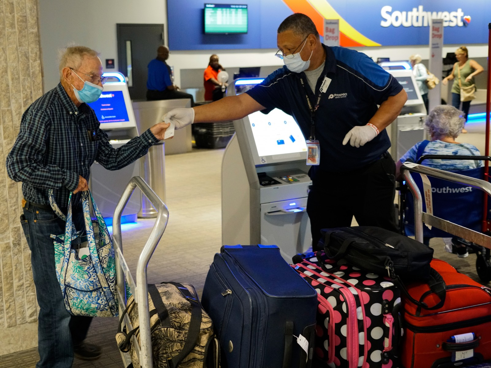 Employee assisting passenger with masks