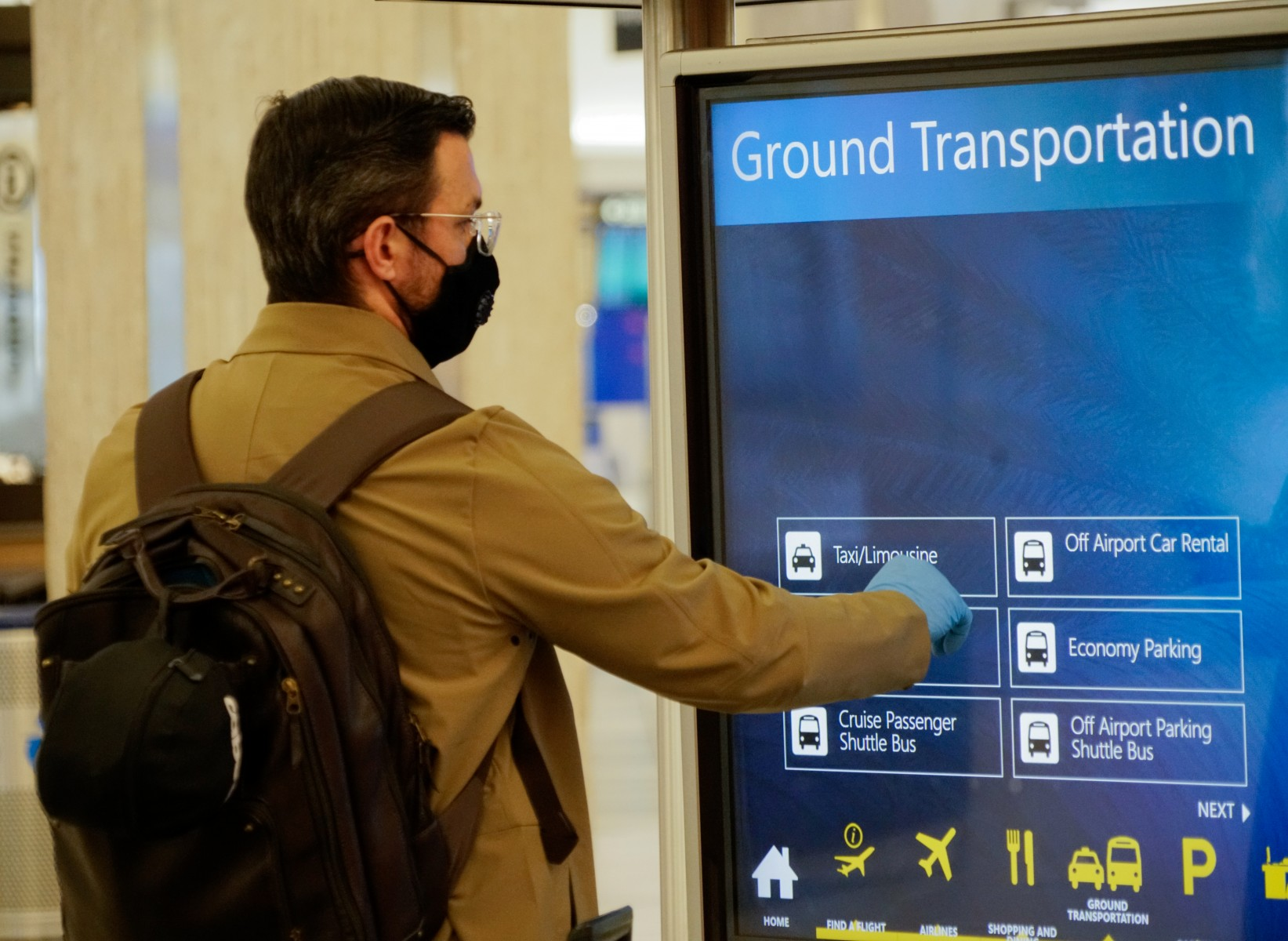 Passenger using touch-screen in Main Terminal with gloves and mask
