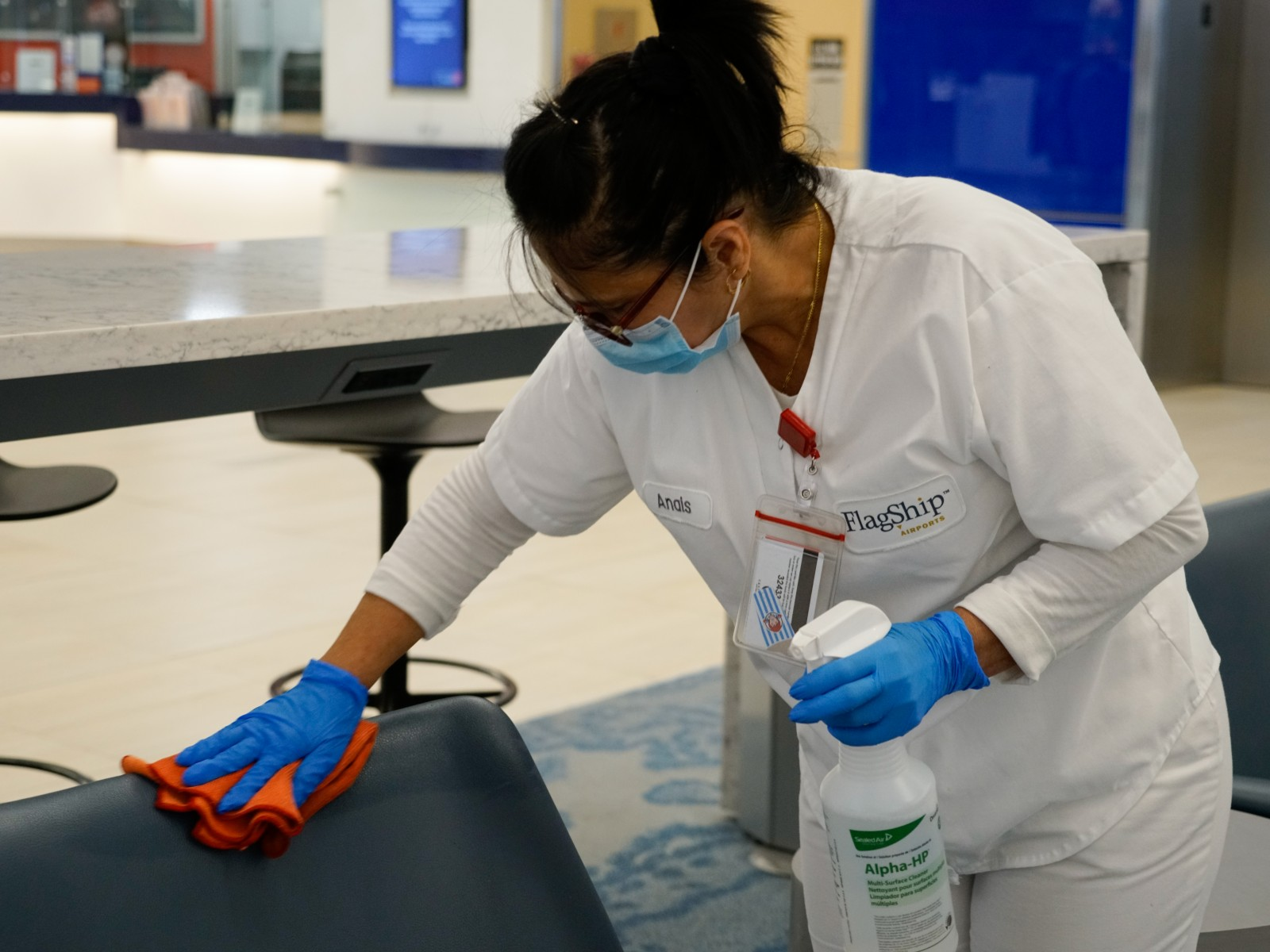 Tampa International Airport employee sanitizing high-touch area