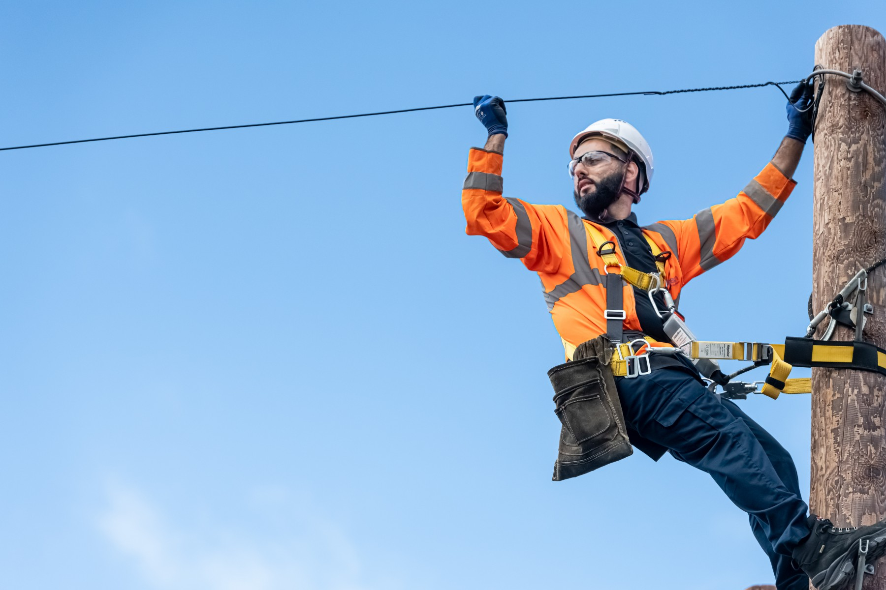 Openreach engineer installing overhead fibre cables
