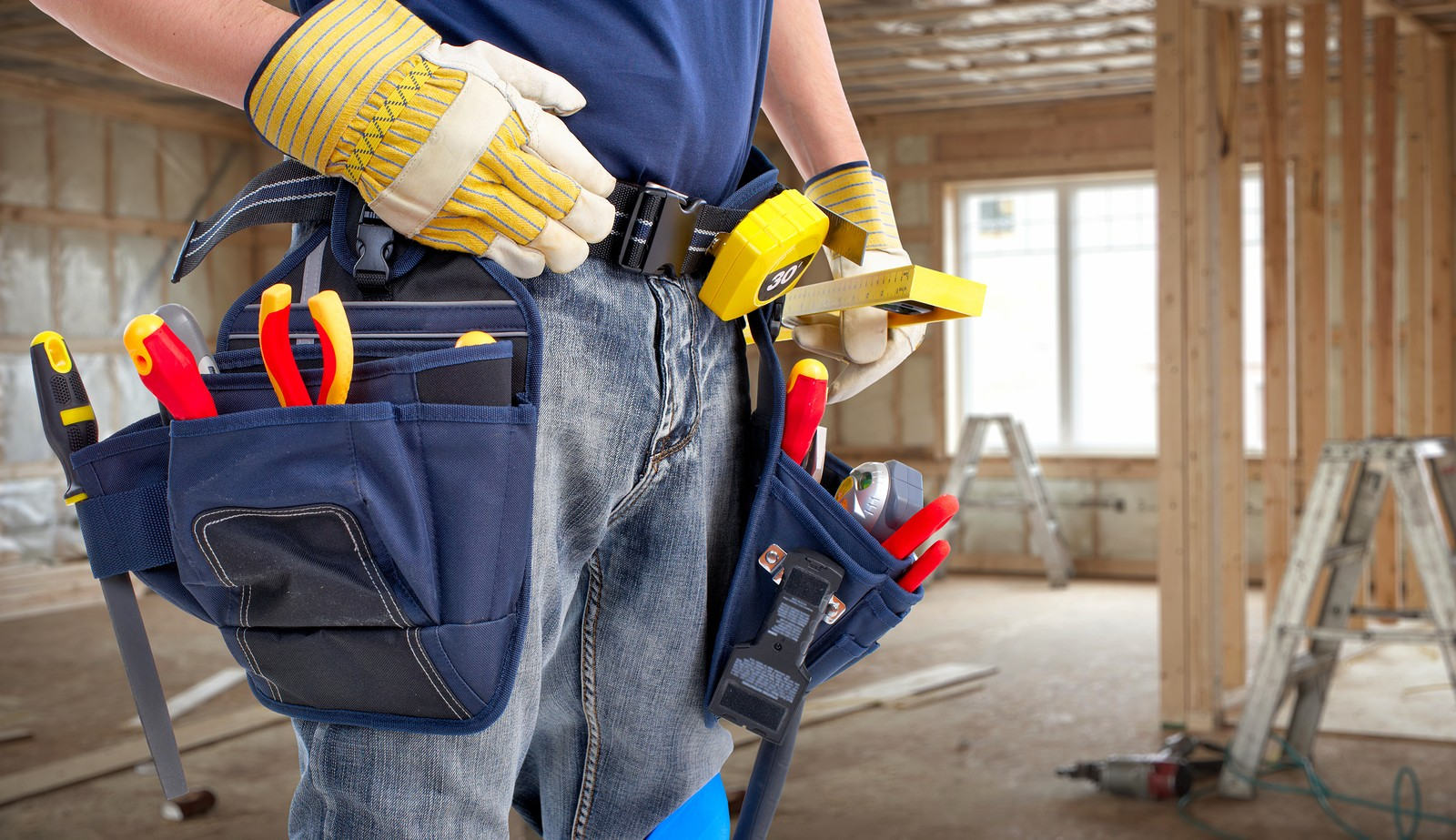 Worker with construction tools. House renovation background.
