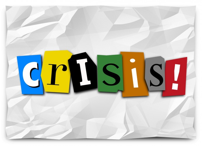Crisis word in cut out letters on crumpled paper like a ransom note to convey a message of emergency