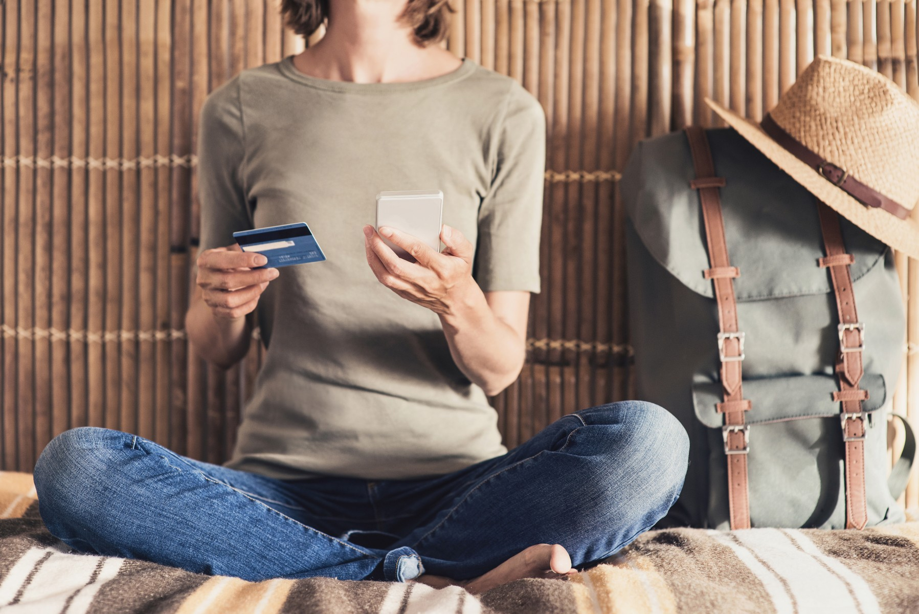 Young woman on vacations using phone and credit card